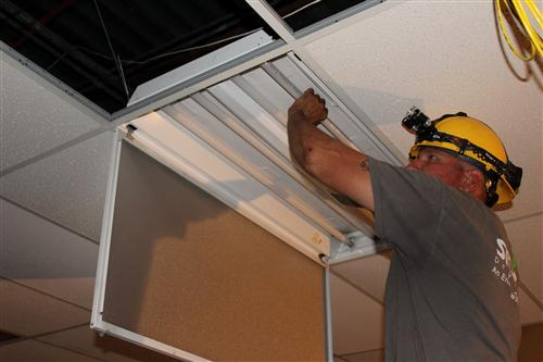 APS worker removes and installs energy efficient lighting